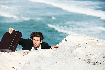 Buy stock photo Businessman climbing up the side of a cliff  with his his briedcase with the ocean in the background