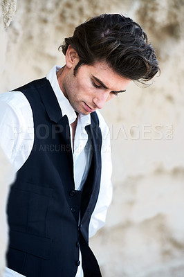 Buy stock photo Closeup of a handsome young male wearing a vest and looking downwards