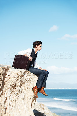 Buy stock photo Pensive young man sitting with his briefcase on the edge of a cliff overlooking the ocean