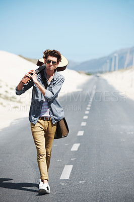 Buy stock photo Trendy young man holding his guitar over his shoulder walking down the road