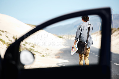 Buy stock photo Rear-view of a young man walking down the road holding a map, framed by a car door window in the foreground