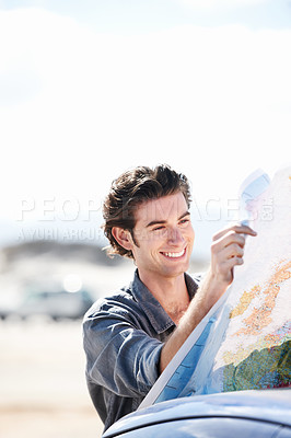 Buy stock photo Handsome young man smiling while inspecting a map next to his car