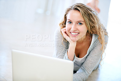 Buy stock photo A cute young blonde lying on the floor and browsing her laptop
