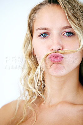 Buy stock photo A young beauty fooling around by putting her hair on her upper lip and pouting