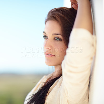 Buy stock photo A beautiful young woman leaning on a white wall outside