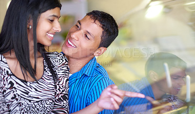 Buy stock photo Shot of an affectionate young couple looking at ice cream through the window of a shop