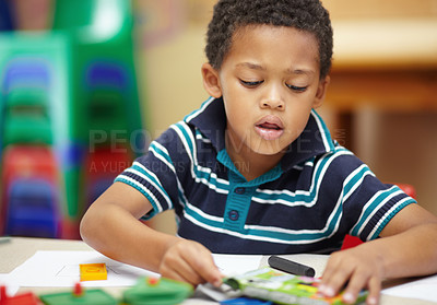 Buy stock photo Pre-school african american boy concentrating on his drawings with his crayons and shapes