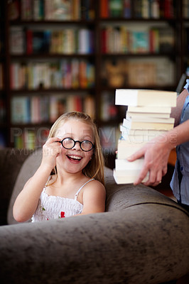 Buy stock photo A cute little girl wearing glasses smiling as a woman hands her a stack of books