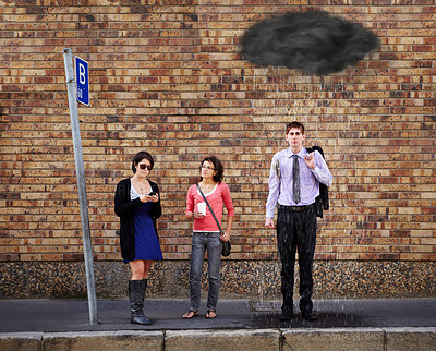 Buy stock photo A black rain cloud over the young man's head standing at the bus stop