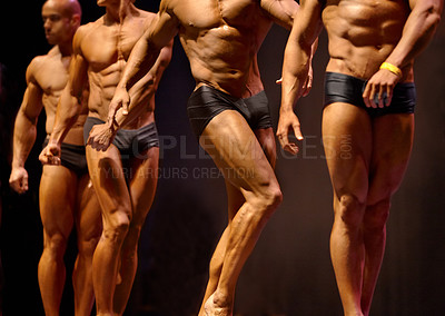 Buy stock photo Cropped view of a group of bodybuilding contestants flexing their muscles while on stage