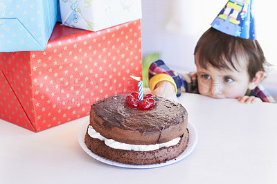 Buy stock photo A cute little boy looking at his birthday cake and presents on the table