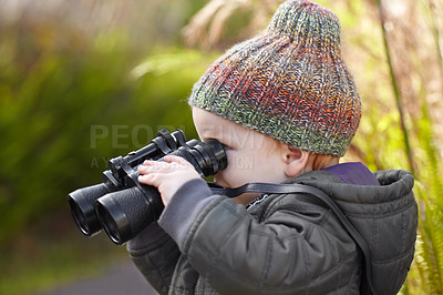 Buy stock photo A cute little boy looking through binoculars
