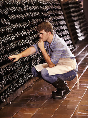 Buy stock photo A young wine maker counting the bottles of wine in his cellar