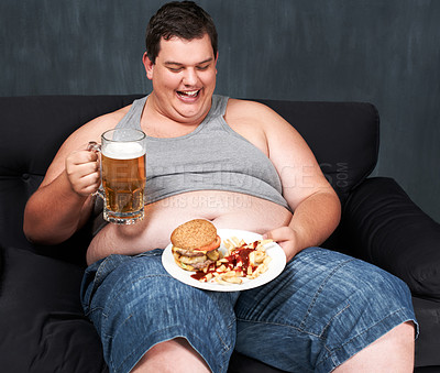 Buy stock photo An obese young man sitting on a sofa and gorging himself on beer and fast food