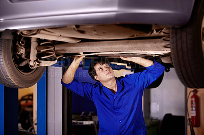 Buy stock photo A young male mechanic looking at the steering column under a car