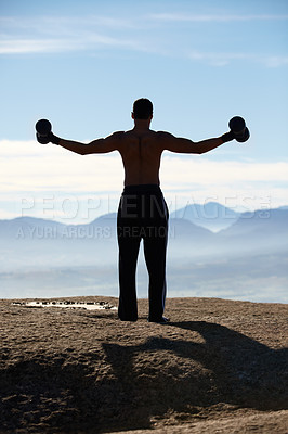 Buy stock photo Rearview of a man standing on a mountain top holding out dumbells on either side of him