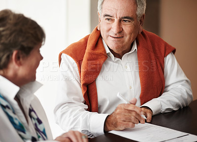 Buy stock photo A senior man and his wife filling out forms at a hotel reception desk