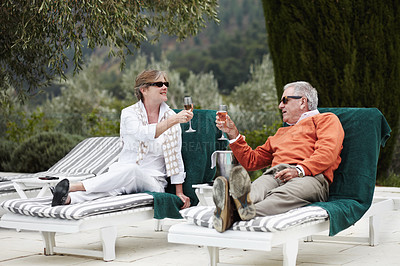 Buy stock photo A senior couple toasting to their vacation by the hotel pool