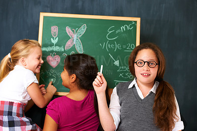 Buy stock photo Portrait of a cute brunette schoolgirl with two friends playing on the chalkboard in class