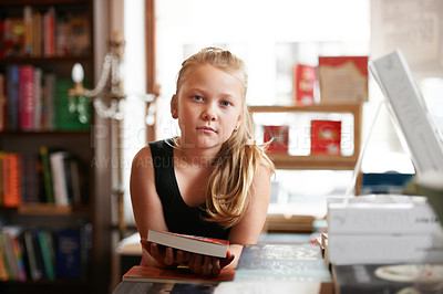 Buy stock photo Portrait of a cute blonde girl standing with a book in the library