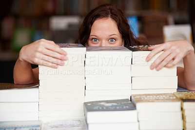 Buy stock photo Portrait of a young woman peeking over stacks of paperback books
