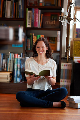 Buy stock photo Portrait of a young woman sitting cross-legged on the floor of a bookstore and reading