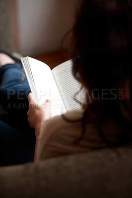 Buy stock photo A rearview shot of a young woman reading a book
