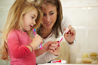 Buy stock photo Cute little girl getting ready to brush her teeth with her mom