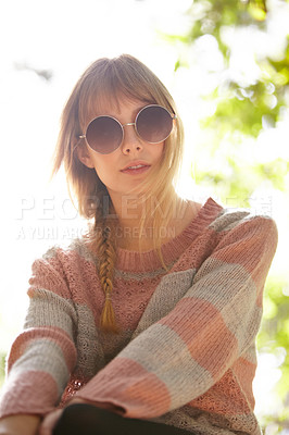 Buy stock photo Shot of an attractive young woman wearing sunglasses and sitting outside