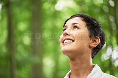 Buy stock photo A closeup shot of an attractive young woman looking upwards into the canopy of a forest