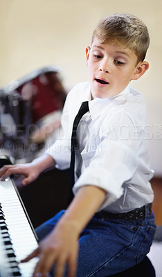 Buy stock photo Young boy playing the piano diligently