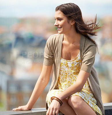 Buy stock photo Pretty young woman sitting on a rooftop and looking away