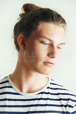 Buy stock photo Young man with his hair in a bun looking away