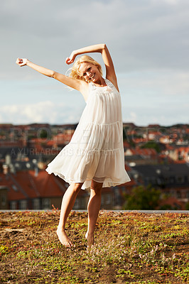 Buy stock photo A fun young woman on a rooftop dancing