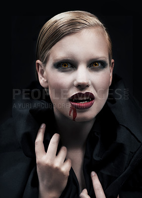 Buy stock photo A provocative female vampire with blood running down her chin against a dark background