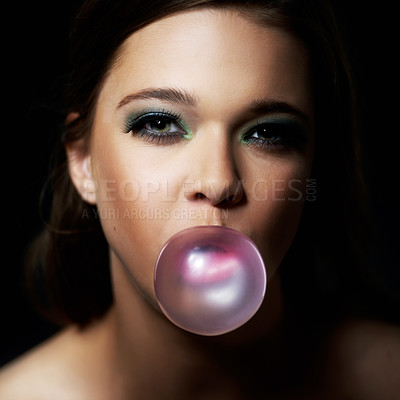Buy stock photo Shot of a young woman blowing a bubble with her gum against a dark background