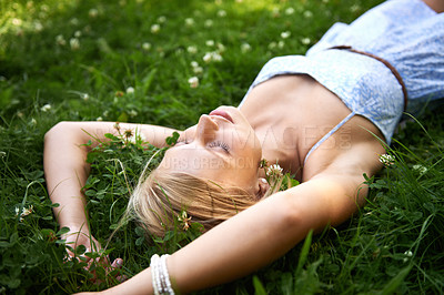 Buy stock photo Pretty young blonde woman lying on the grass while fast asleep