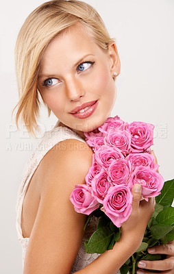 Buy stock photo An attractive young woman holding a bouquet of pink roses