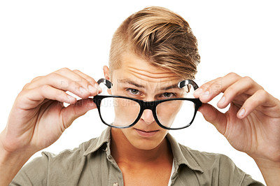 Buy stock photo Studio shot of a young man looking through a pair of glasses he is holding in front of him