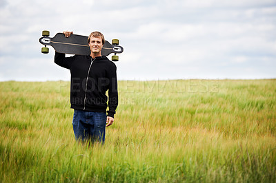 Buy stock photo Young skateboarder holding his board on his shoulder while standing in a field