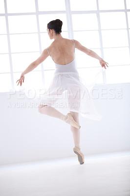 Buy stock photo Graceful young ballerina in white dancing en pointe