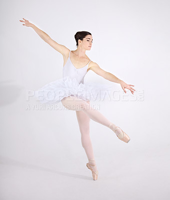 Buy stock photo Dedicated young ballerina dancing en pointe against a white background