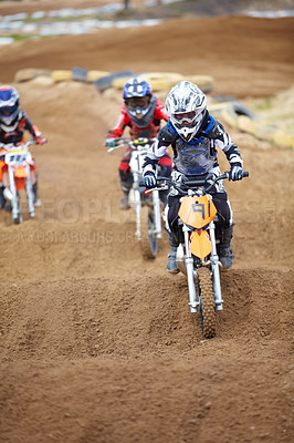 Buy stock photo Three motocross riders riding in close proximity to each other