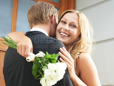 Buy stock photo A beautiful woman with a bunch of flowers in her hand hugs her boyfriend and smiles