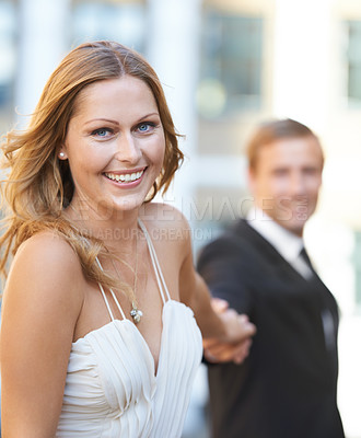 Buy stock photo A portrait of a beautiful woman walking hand in hand with her boyfriend
