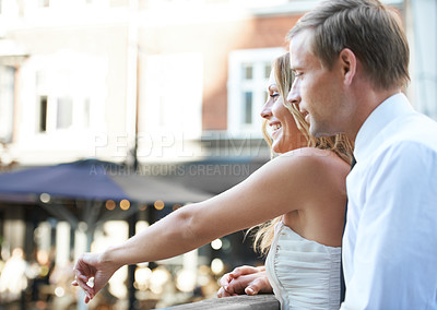 Buy stock photo A beautiful couple stand together at a bridge and look down at the happenings below