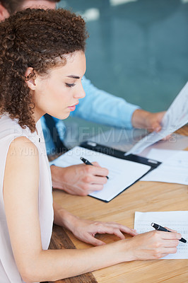 Buy stock photo Two businesspeople working together on some documents