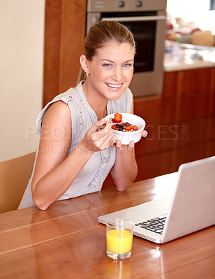 Buy stock photo A pretty young woman eating breakfast and using her laptop in the kitchen