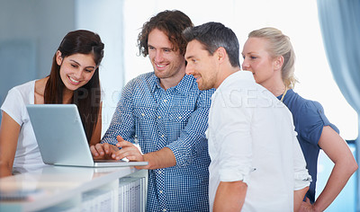 Buy stock photo Cropped shot of four coworkers gathered around a laptop in the office