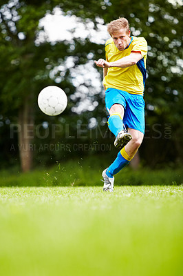 Buy stock photo Shot of a soccer player kicking the ball with gusto